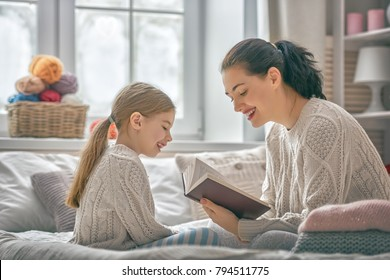 Winter portrait of happy loving family. Pretty young mother reading a book to her daughter at home.