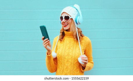Winter portrait happy smiling woman holding phone in wireless headphones listening to music wearing yellow knitted sweater, white hat with pom pom, heart shaped sunglasses on blue wall background