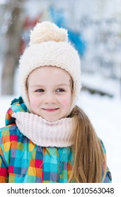 Winter portrait of a little girl in the background of snow.