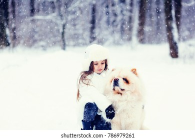 winter portrait of a little girl and a chow chow dog in the forest