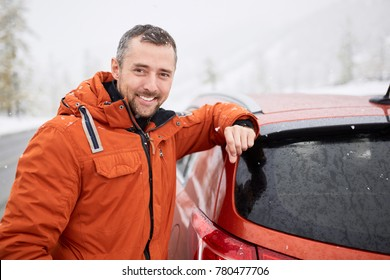 Winter portrait of a man with a car. The man is traveling on the road