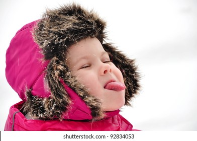 Winter portrait of small girl in pink snowsuit and warm hat catching snowflakes with a tongue
