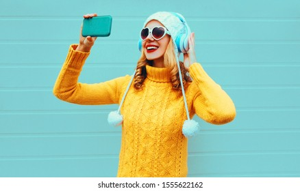 Winter portrait smiling woman taking selfie picture by phone while listening to music in wireless headphones wearing yellow knitted sweater, white hat, heart shaped sunglasses on blue background