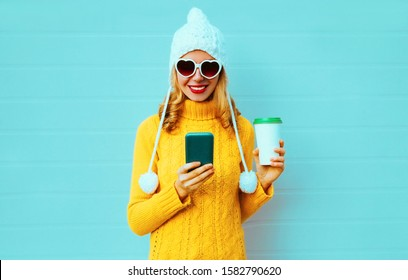 Winter portrait smiling young woman with phone and coffee cup wearing yellow knitted sweater, white hat with pom pom, heart shaped sunglasses on blue background