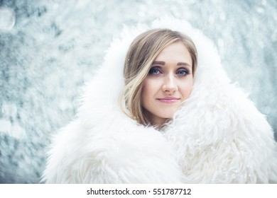 Winter portrait of a woman in real fur coat. Extremely shallow depth of field, subtle toning,