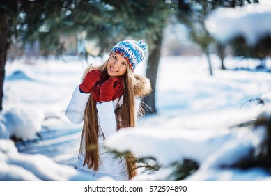 Winter portrait of young beautiful blond woman wearing knitted snood covered in snow. Snowing winter beauty fashion concept.