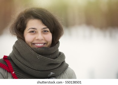 Winter portrait of young beautiful brunette girl with scarf covered in snow. Snowing winter beauty fashion concept.