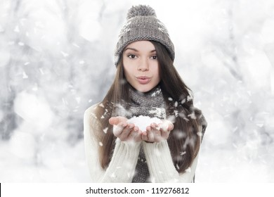 Winter portrait. Young, beautiful woman blowing snow toward camera on winter background