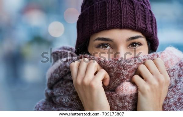 Retrato de invierno de una joven hermosa mujer cubriendo la cara con bufanda de lana. El cierre de una chica feliz sintiendo frío afuera en la ciudad. Mujer joven sosteniendo una bufanda y mirando la cámara.