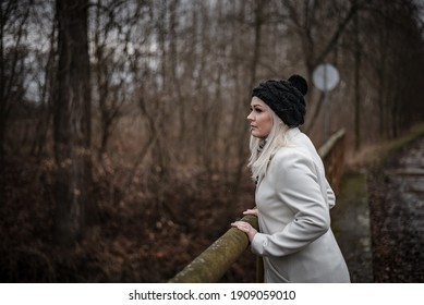 Winter portrait of young blonde woman enjoying view during walk out of town to social distance