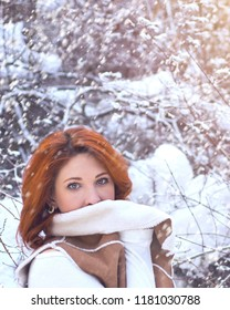 Winter portrait of a young fashionable beautiful girl with red hair. Woman breathing on her hands to keep them warm at cold winter day.