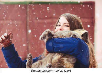 Winter portrait of a young woman with a cat. Beauty Joyous Model A girl laughs and is happy to have a dark red background. Beautiful young woman outdoors. Enjoy nature, in winter.