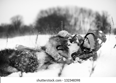 winter portrait of young woman with her Alaskan Malamute dog