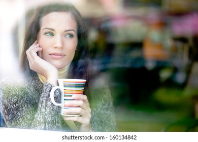 Winter portrait of a young woman looking out the window enjoying a hot cup of tea / coffee
