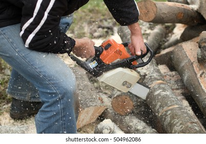Winter preparation. Man lumberjack holding motorized chainsaw and cutting through wood. Provision of firewood for the winter.