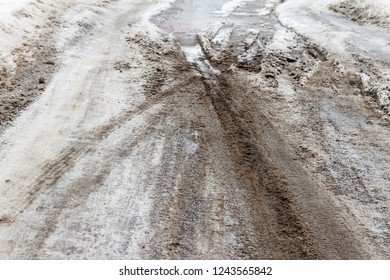 Winter puddles and snow slush on road with traces of tires during the thaw
