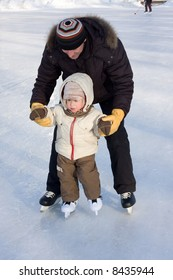 Winter recreation. Father and child skating on rink. Focus is on boy's face