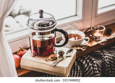 Winter relax at cozy home. Glass teapot with hot tea, book, glasses, candle and blanket by the window, snow outside. Peaceful hygge atmosphere, moody light, slow life philosophy concept.