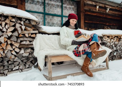 Winter relax - woman sitting outside a cottage and reading a book on a snowy day. Woman enjoying time on her own on a cold winter day.