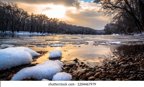 Winter River Sunset. Snow and ice float down the Grand River in Grand Rapids, Michigan, USA. Seasonal beauty landscape background with copy space.