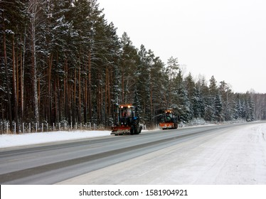 Winter road in a coniferous forest covered with snow. Two snowplows cleaning snow