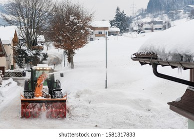 Winter road maintenance. Tractor with milling and rotor snowplow equipment cleaning the street from the snow cover.