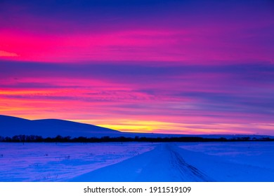 Winter road with mountain during amazing vivid saturated beautiful sunset sky in pink, purple and blue colors. Sunset background - Shutterstock ID 1911519109