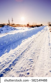 Winter road in the Russian countryside at sunset against the sky in the vicinity of the power plant distribution