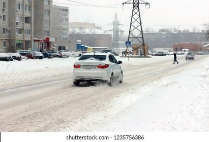 Winter road in the snow. A car is approaching a pedestrian crossing.crosswalk in winter