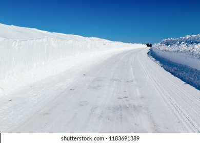 Winter road with tall snowbanks on each side.