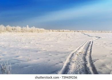 Winter road, through a field covered with snow, under a blue sky. Winter landscape.