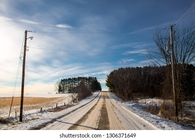 Winter road through snowy fields and forests