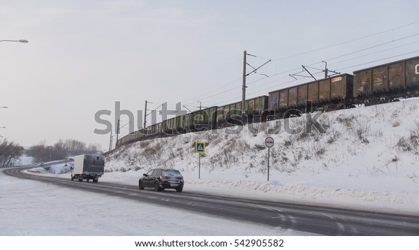 Winter road and train on railroad in snow-covered winter village at sunny day, wide angle