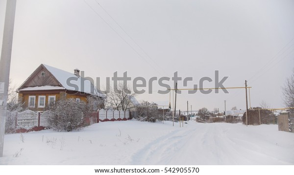 Winter road at typical Russian countryside - village in center of Volga, snow cold day, wide angle