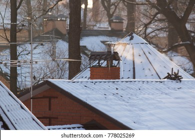 Winter rooftops with snow and smoke on sunny day