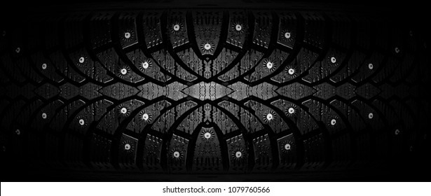 Winter rubber with spikes on a black background close-up. guaranteed safety in winter. Winter tire on the background of racks with tires.