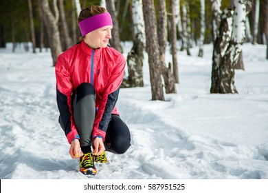 Winter runner getting ready running tying shoe laces. Beautiful fitness model training outside. Copy space on snow.