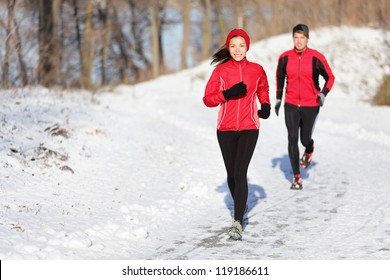 Winter running exercise couple. Runners jogging in snow. Young asian woman fitness model and caucasian man.