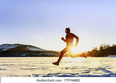 winter running male runner in background of mountains and sunrise
