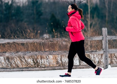 Winter running in park: happy woman runner jogging in snow, outdoor sport and fitness concept.