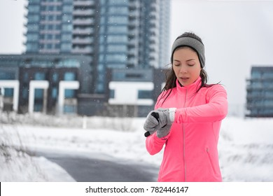 Winter running smartwatch fitness girl in cold snow weather jogging outside on street wearing smart watch and windproof clothes with gloves, headband, pink jacket in city background.