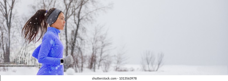 Winter running smartwatch woman in cold snow weather jogging outside wearing windproof clothes with gloves, headband, winter tights and wind jacket in white snowfall background.