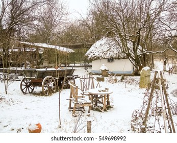 Winter rural scenery: snow covered buildings with a thatched roof, wooden arbors, the snow on a cart.