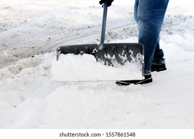 winter safety -  a man shoveling the snow from a sidewalk