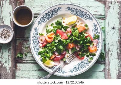 Winter Salad with Watercress, Salmon, Radish, Grapefruit, lemon and Turmeric Sauce. Healthy Food