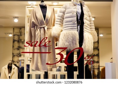 Winter sale. Window shop with dressed mannequin, text Sale and 30 percent discount