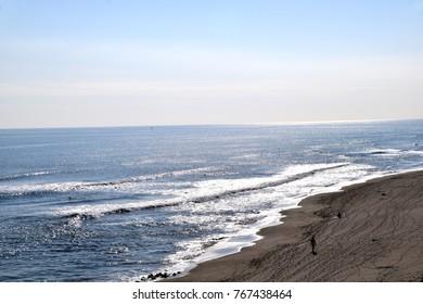 Winter sandy beach and surfer.