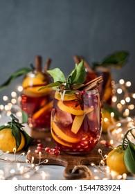 Wintersangria auf dunklem Weihnachtshintergrund. Schmeichelvoll mit Sangria und Brillen mit Obstscheibe, Granatapfel und Gewürzen. Kopiert Platz für Text oder Design. Vertikal.