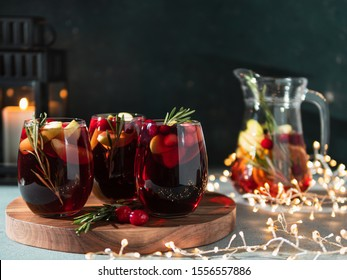 Winter sangria on dark christmas holiday background. Jugful of sangria and glasses with fruit slice, cranberry and rosemary. Copy space for text or design. Horizontal.