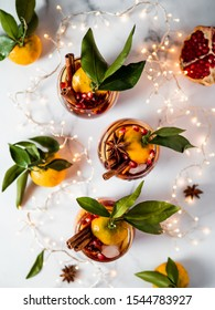 Winter sangria on white marble background. Holiday sangria in glasses with fruit slice, pomegranate and spices on decoration lighting chain tabletop. Top view or flat lay. Vertical.